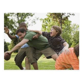 People tackling while playing football postcard
