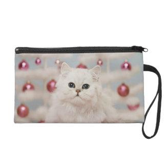 Persian cat sitting on pink pillow wristlet