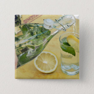 Person pouring water (mint-filled) into a glass 15 cm square badge