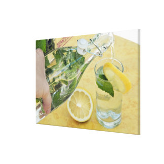 Person pouring water (mint-filled) into a glass canvas print