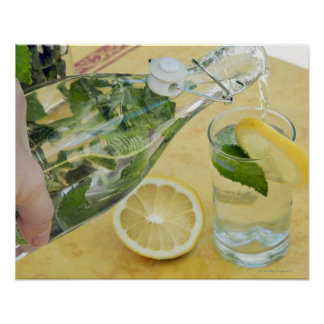 Person pouring water (mint-filled) into a glass poster