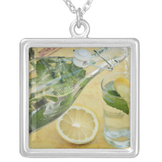 Person pouring water (mint-filled) into a glass silver plated necklace