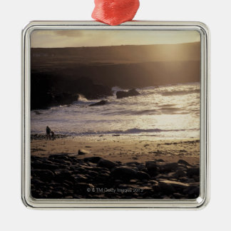 person with child walking on rocky beach christmas ornament