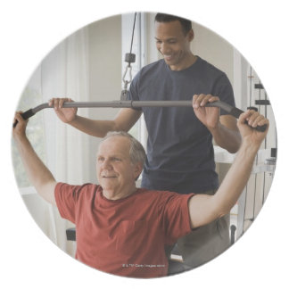 Personal trainer with man in home gym dinner plates