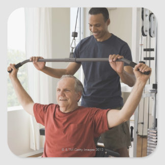Personal trainer with man in home gym square sticker