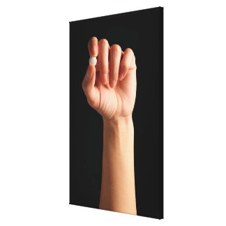 Persons hand holding a white pill between the canvas print