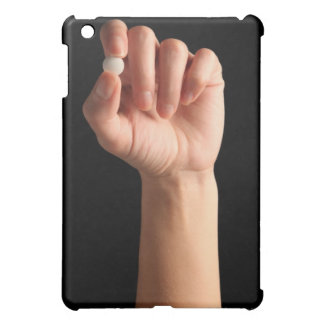 Persons hand holding a white pill between the iPad mini case