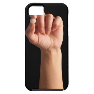 Persons hand holding a white pill between the iPhone 5 cover
