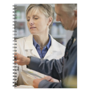 Pharmacist helping customer with medicine spiral notebook