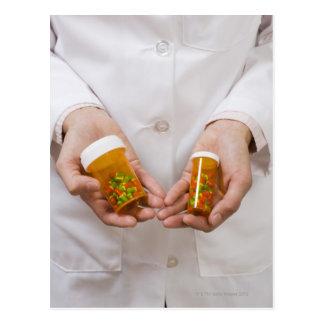 Pharmacist holding pill bottles postcard