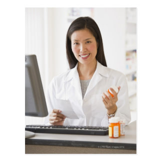 Pharmacist holding prescription medication postcard