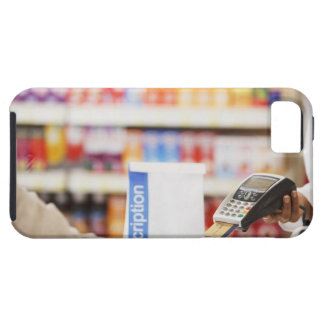 Pharmacist holding security device for customer iPhone 5 case