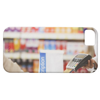 Pharmacist holding security device for customer iPhone 5 cover
