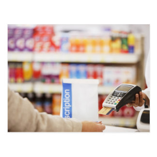 Pharmacist holding security device for customer postcard