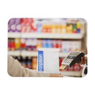Pharmacist holding security device for customer rectangular photo magnet