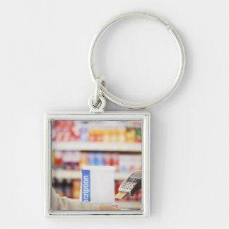 Pharmacist holding security device for customer Silver-Colored square key ring