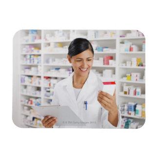 Pharmacist in drug store holding clipboard magnet