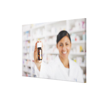 Pharmacist in drug store holding out pill bottle canvas print