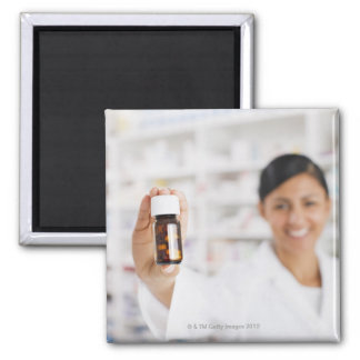 Pharmacist in drug store holding out pill bottle square magnet