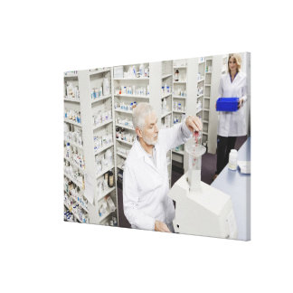 Pharmacist pouring pills into counting machine canvas print