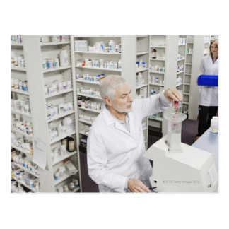 Pharmacist pouring pills into counting machine postcard