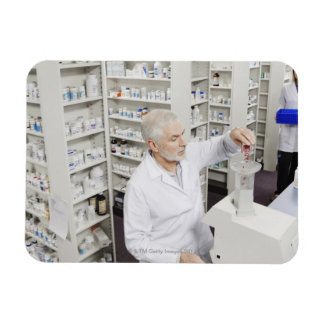 Pharmacist pouring pills into counting machine rectangular photo magnet