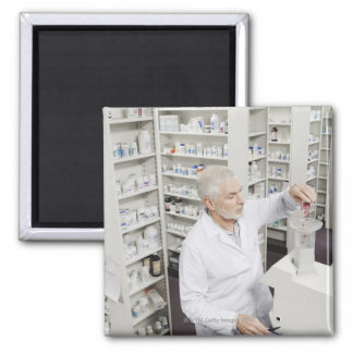 Pharmacist pouring pills into counting machine square magnet