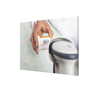 Pharmacist scanning pill bottle with a barcode canvas print