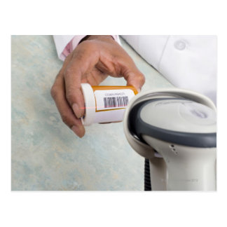 Pharmacist scanning pill bottle with a barcode postcard