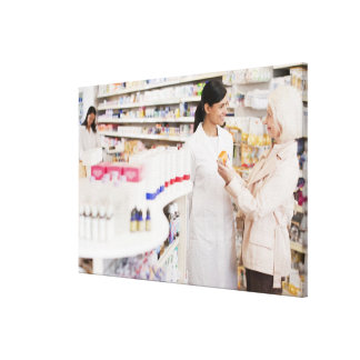 Pharmacist talking to customer in drug store canvas print