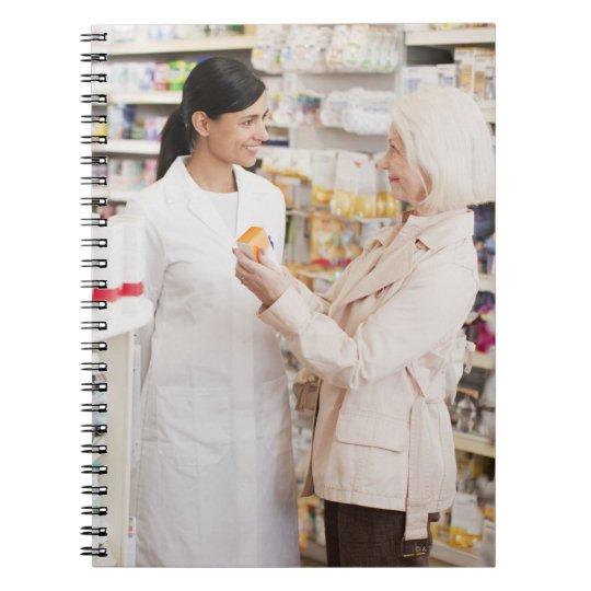 Pharmacist talking to customer in drug store notebook