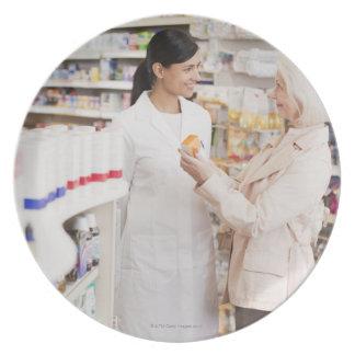 Pharmacist talking to customer in drug store plate