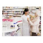 Pharmacist talking to customer in drug store postcard
