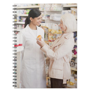 Pharmacist talking to customer in drug store spiral notebooks