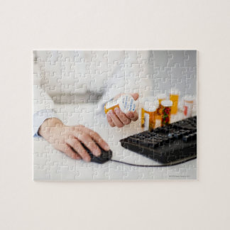 Pharmacist with pill bottles at computer jigsaw puzzle