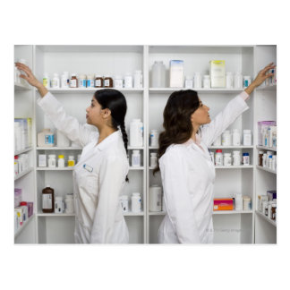 Pharmacists reaching for medication on shelves postcard