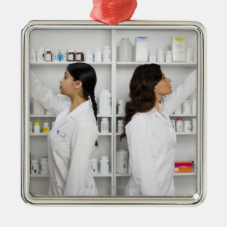 Pharmacists reaching for medication on shelves Silver-Colored square decoration