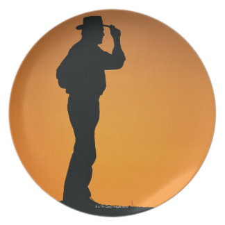 Photo, silhouette of a cowboy with his hand on plate