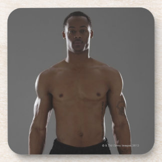Physically fit man lifting dumbbells coaster