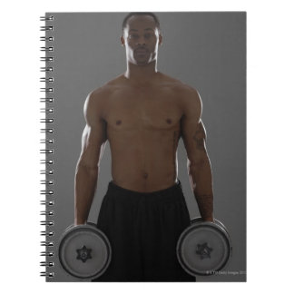 Physically fit man lifting dumbbells notebook