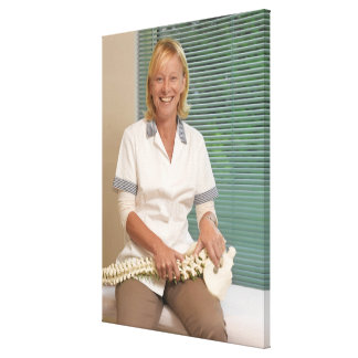 Physiotherapist with model of spine canvas print