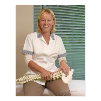Physiotherapist with model of spine postcard