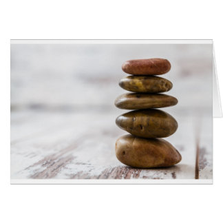 Pile of dark colored stones on white background greeting card