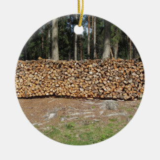 Pile of firewood with forest background round ceramic decoration