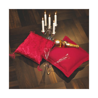Pillows, candlesticks and champagne on dark parque canvas print