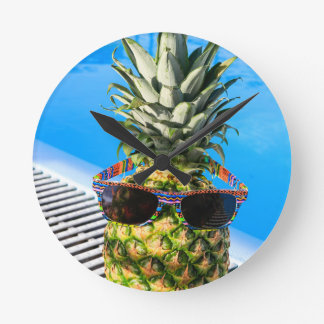 Pineapple wearing sunglasses at swimming pool round clock