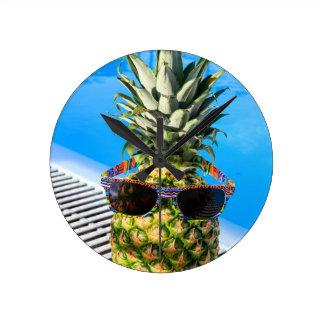 Pineapple wearing sunglasses at swimming pool wall clocks