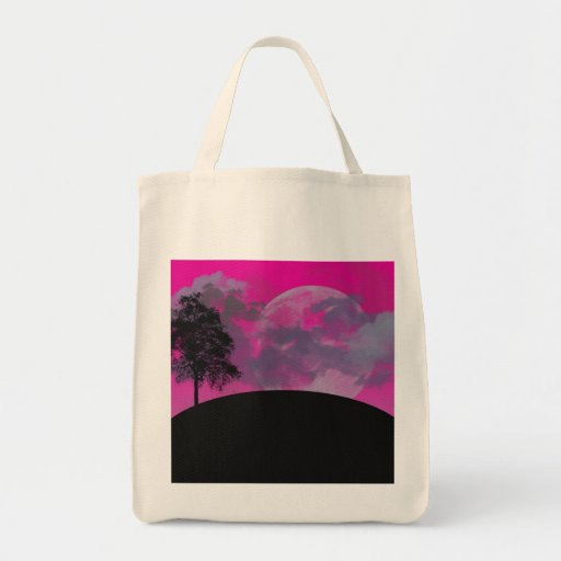 Pink fantasy moon, clouds & black tree silhouette tote bags