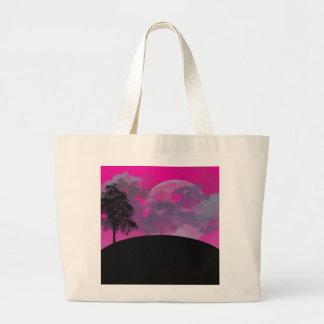 Pink fantasy moon, clouds & black tree silhouette tote bag