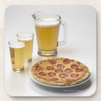 Pitcher and two pints of beer beside pepperoni coaster